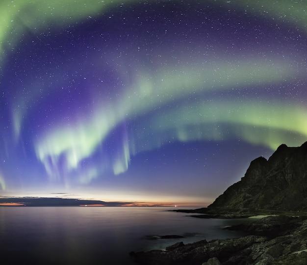 Noite polar de tirar o fôlego acima do mar e das rochas na noruega