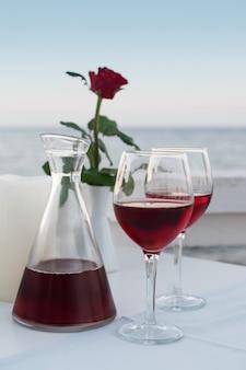 Noite romântica beber vinho tinto no restaurante pelo mar ainda vida