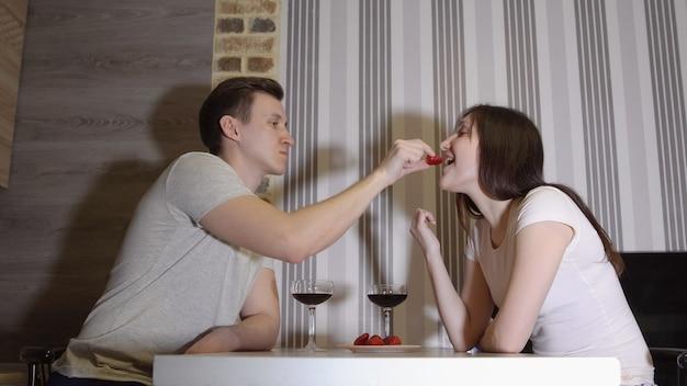 Noite romantica. jovem casal em uma mesa bebendo vinho e comendo morangos.