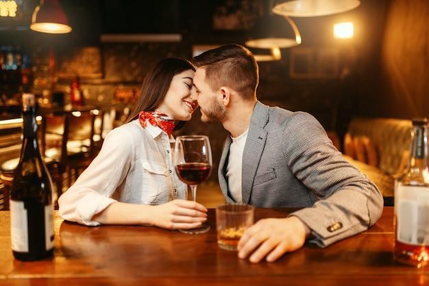 Noite romântica no bar, amo o casal se beijando no balcão de madeira.