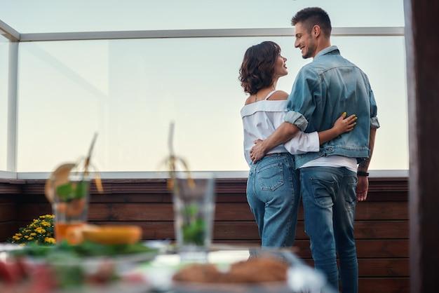 Noite romântica vista traseira de um jovem casal com roupas casuais olhando um para o outro