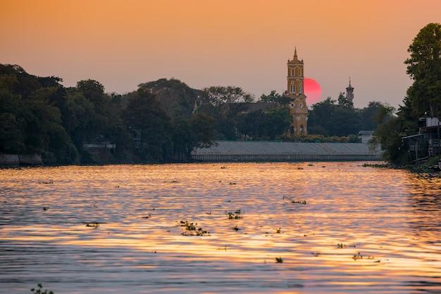 Noite vista para o rio, pôr do sol e uma igreja em phra nakhon si ayutthaya, tailândia