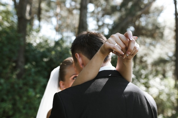 Noiva abraçando noivo de pé lá fora