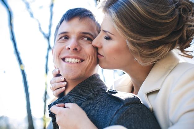 Noiva abraçando noivo em vista de perto do parque
