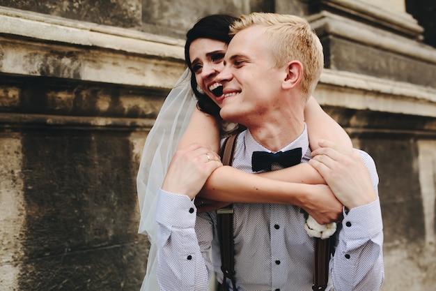Noiva, abraçando o namorado por trás e rir