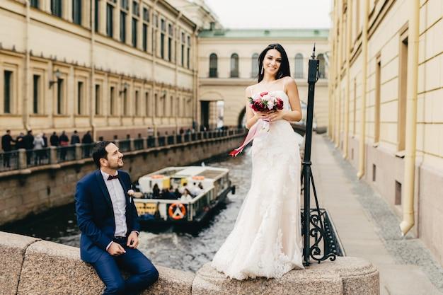 Noiva adorável fofa, com longos cabelos escuros, usa vestido de noiva, mantém lindo buquê de flores, fica na ponte e o marido que fica perto dela
