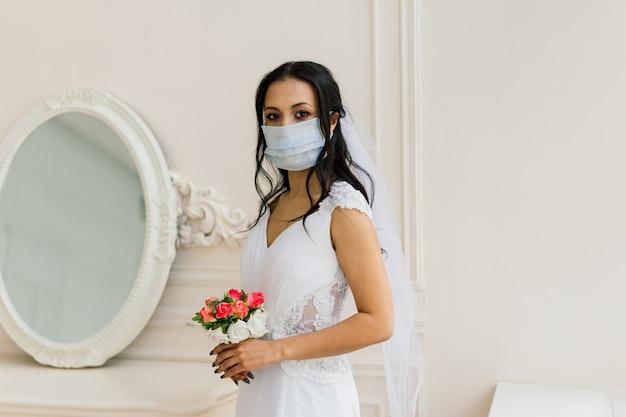 Noiva afro-americana de vestido, máscara e pela manhã se preparando para o casamento em quarto de hotel