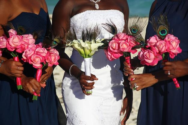 Noiva afro-americana em um vestido branco com damas de honra segurando buquês de flores coloridas no dia do casamento ao ar livre.