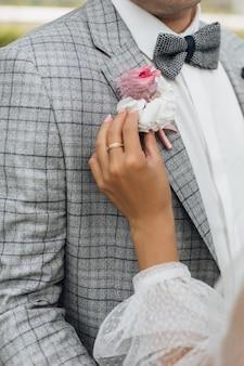 Noiva agarra a flor na lapela da jaqueta do noivo, sem rosto