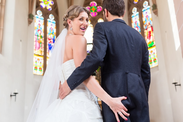 Noiva agarrando o rabo do noivo no casamento na igreja