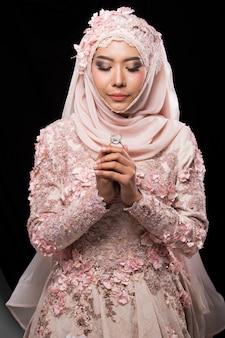 Noiva árabe muçulmana encantadora asiática em lace bead bordado sweet pink vestido de noiva rosa rosa velho e lenço na cabeça hijab, close-up na moda maquiagem rosto de olhos, estúdio iluminação fundo preto isolado.