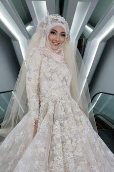 Noiva árabe muçulmana encantadora asiática em vestido de noiva amarelo cremoso bordado de cordão de laço e lenço de cabeça hijab, close-up em rosto de olhos de maquiagem de moda, fundo cinza de iluminação de estúdio isolado.