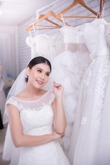 Noiva asiática jovem experimentando vestido de noiva no casamento moderno
