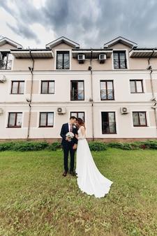 Noiva atraente em vestido branco longo ama seu marido forte perto da bela constituição