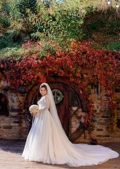 Noiva atraente está de pé na frente da entrada de madeira de um edifício de pedra com folhas coloridas de hera no dia ensolarado