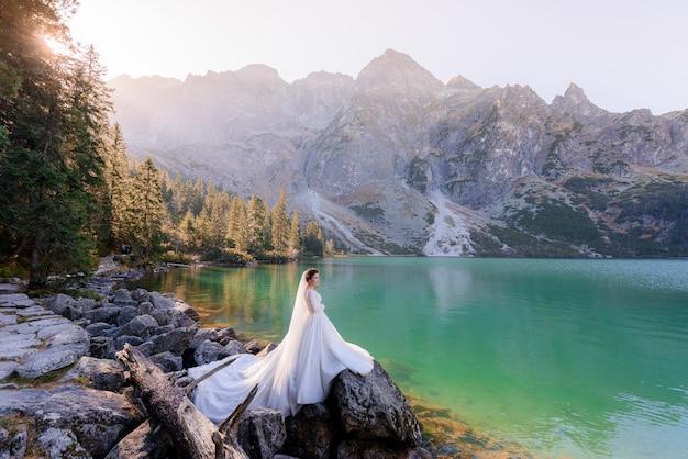 Noiva atraente está de pé perto do lago das montanhas, com vista pitoresca das montanhas de outono