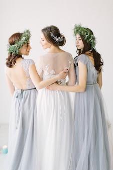 Noiva bonita em um vestido branco de pé e abraçando damas de honra em vestidos cinza e grinaldas