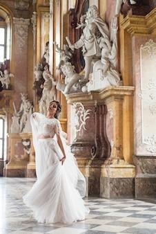 Noiva bonita no castel interior barroco luxuoso.