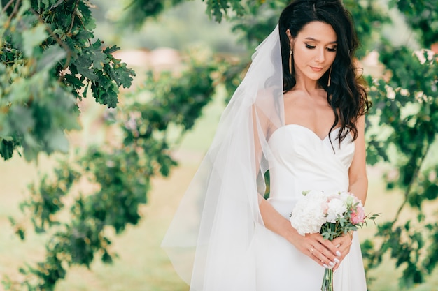 Noiva bronzeada feliz no lindo vestido branco posando com boquet de flores sobre fundo abstrato verde num dia de verão. sessão de fotos ao ar livre nupcial. retrato alegre bonito do estilo de vida da noiva moreno