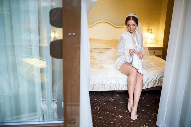 Noiva calça sapatos brancos no dia do casamento