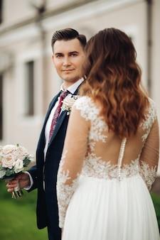 Noiva caucasiana com longos cabelos ondulados em um vestido branco longo cuida de seu marido forte