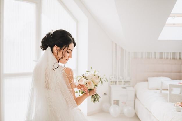 Noiva caucasiana jovem deslumbrante, segurando seu buquê de casamento