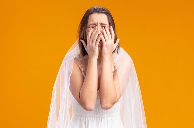 Noiva chateada em lindo vestido de noiva chorando e cobrindo os olhos com as palmas das mãos em pé sobre a parede laranja