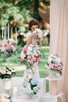Noiva cheira bouquet de casamento em pé antes dos vasos de flores