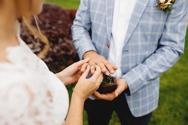 Noiva coloca a aliança no dedo do noivo. boutonniere.