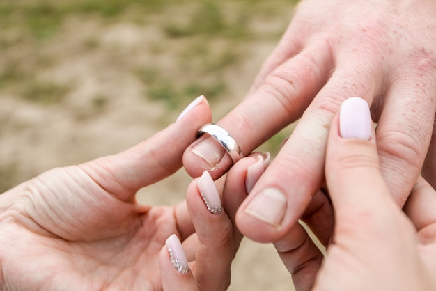 Noiva coloca o anel no dedo do noivo