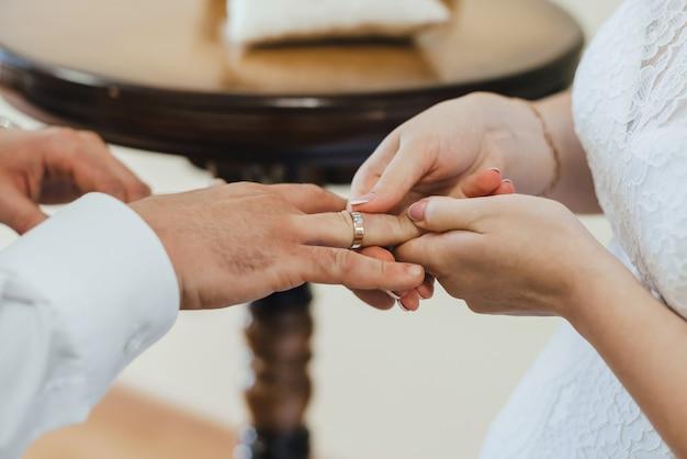 Noiva coloca uma aliança de ouro no dedo do noivo
