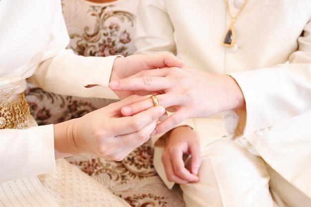 Noiva colocando uma aliança no dedo do noivo