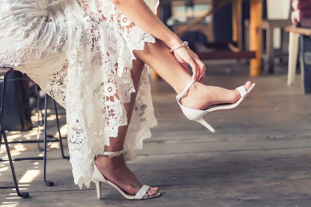 Noiva colocar sapatos de casamento em seus pés