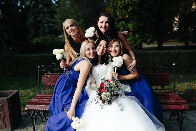 Noiva com amigos posando no banco