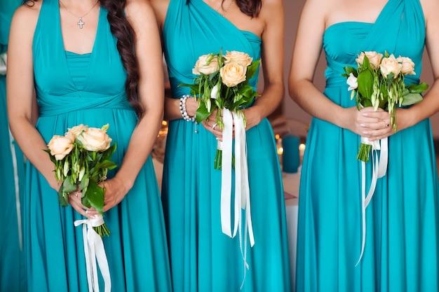 Noiva com as damas de honra segurando um buquê.