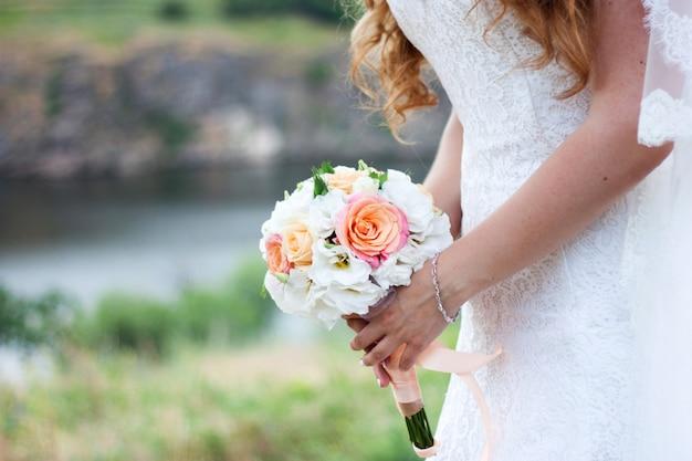 Noiva com buquê de flores cor de rosa e brancas