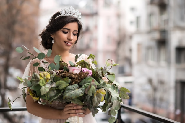Noiva com buquê de flores na varanda entre as ruas da cidade grande