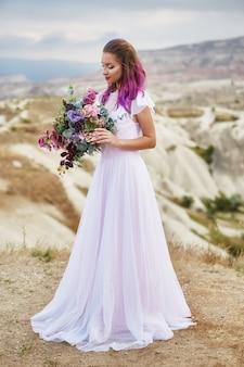 Noiva com cabelo rosa e um longo vestido de noiva segurando um lindo buquê de flores