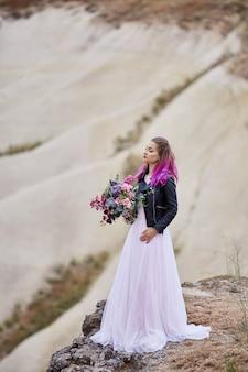 Noiva com cabelo rosa e um vestido de noiva com uma jaqueta segurando um buquê de flores