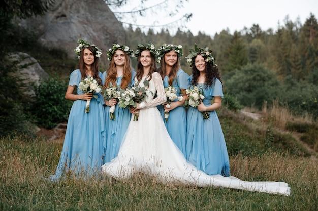 Noiva com damas de honra lindas em vestidos azuis segurando buquês