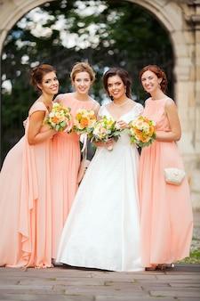 Noiva com damas de honra no parque no dia do casamento