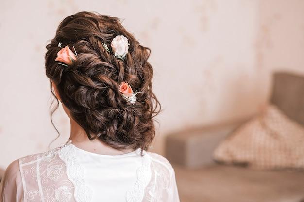 Noiva com penteado e flores no cabelo se senta de costas para a câmera. foto horizontal
