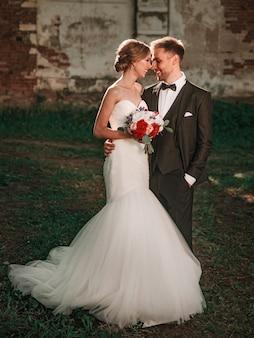 Noiva com um buquê de casamento e o noivo em pé perto da antiga mansão