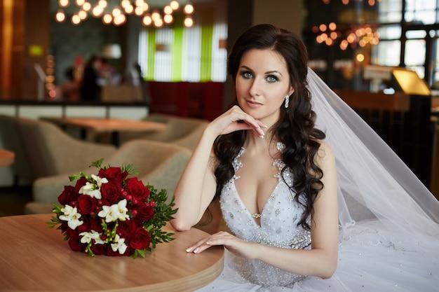 Noiva com um buquê de flores sentado à mesa