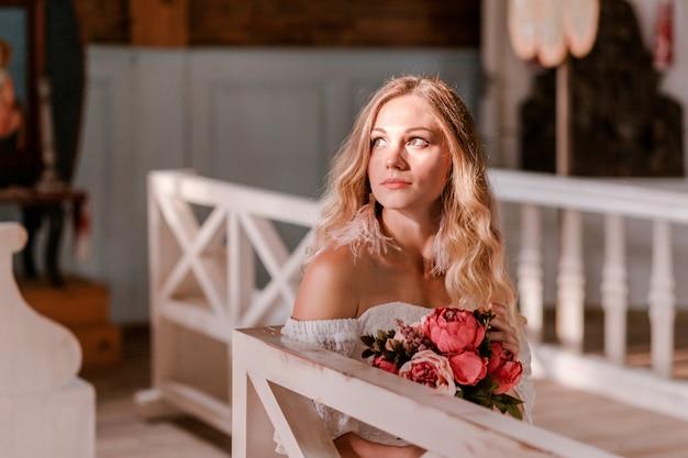 Noiva com um buquê de peônias sentada em um banco