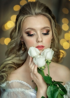 Noiva com um buquê de rosas em um vestido branco sobre um fundo amarelo bokeh, com os olhos fechados.
