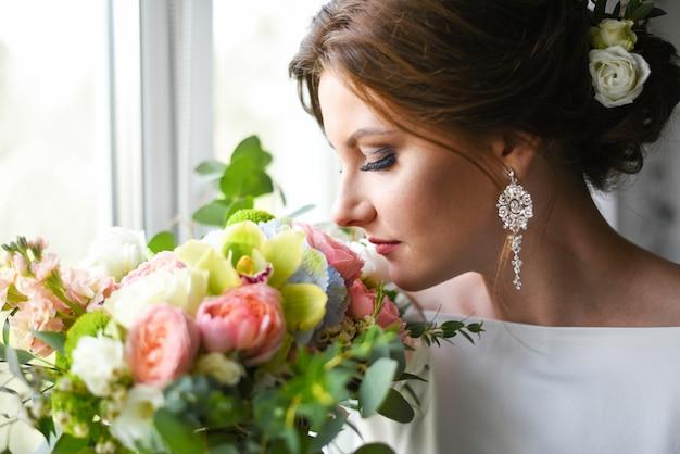 Noiva com um buquê esperando o noivo perto da janela
