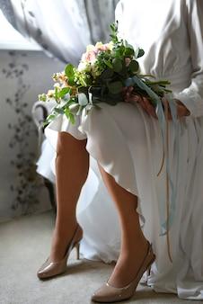 Noiva com um buquê na frente da janela, esperando o noivo