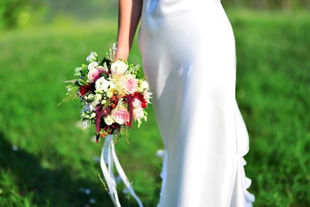Noiva com um lindo buquê de flores em um prado verde.
