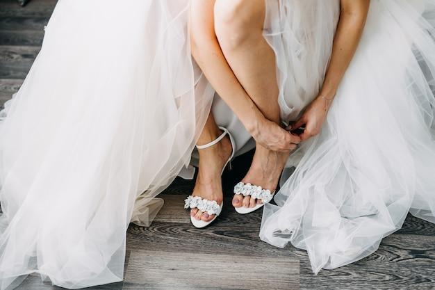 Noiva com um vestido de noiva, calçando os sapatos.